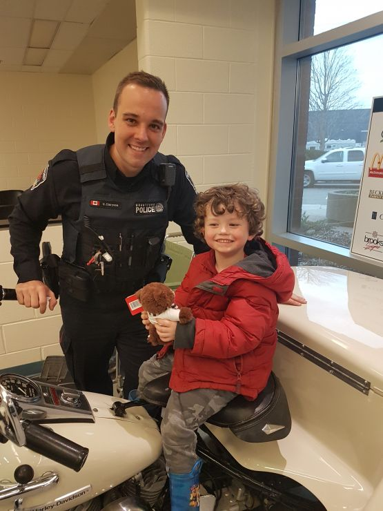 A police officer poses with a young student