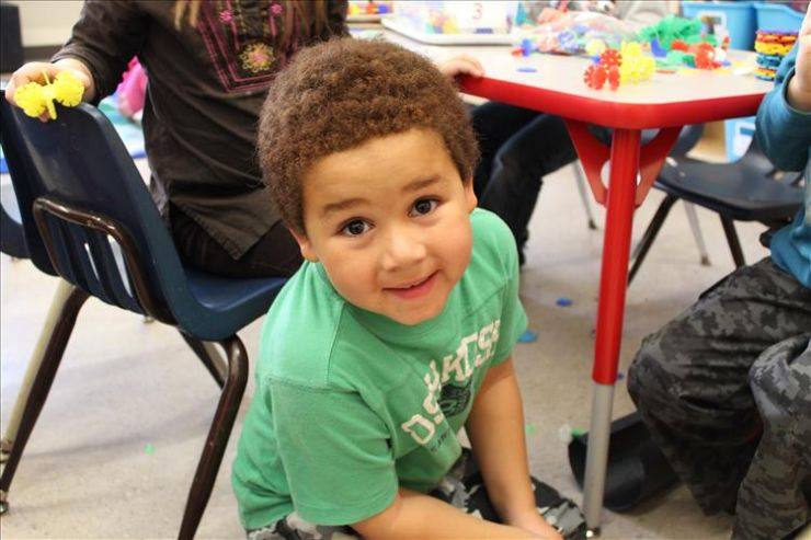 A young boy smiles at the camera in a Kindergarten classroom