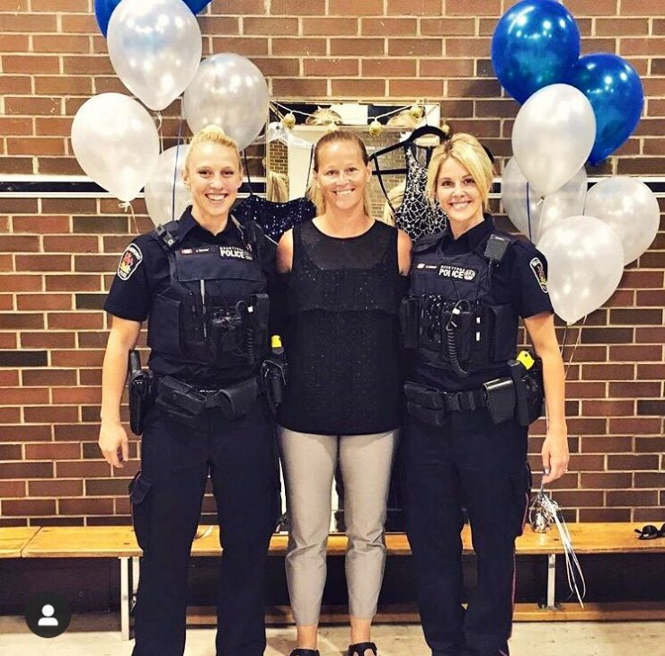 A teacher poses with two police officers