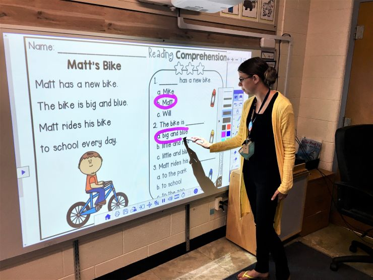 A teacher works on a whiteboard