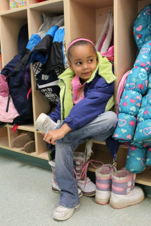 A kindergarten student sits on a bench and puts on her shoes