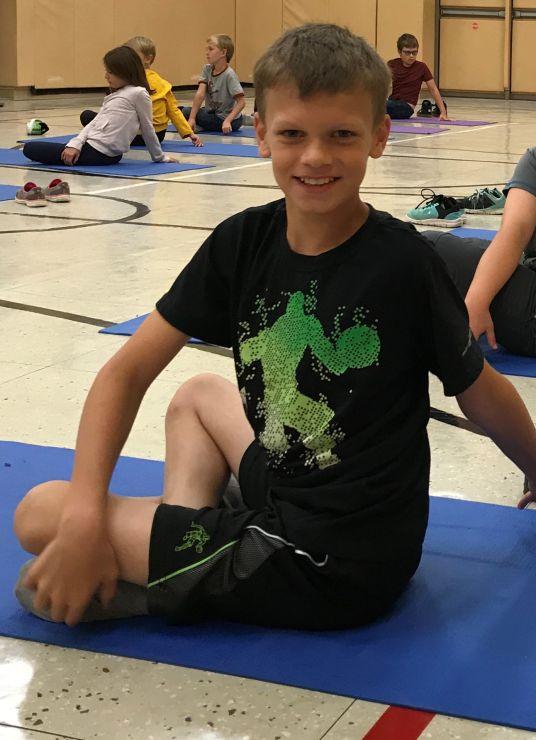 A student twists on a yoga mat