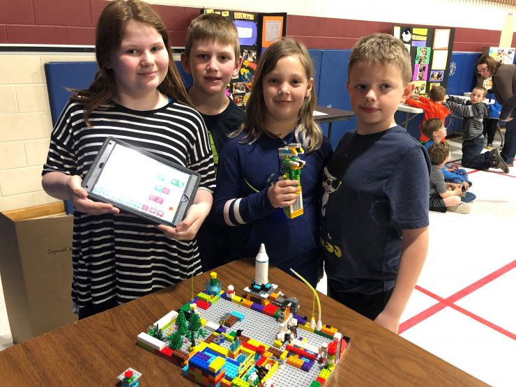 Four students proudly display a completed Lego model