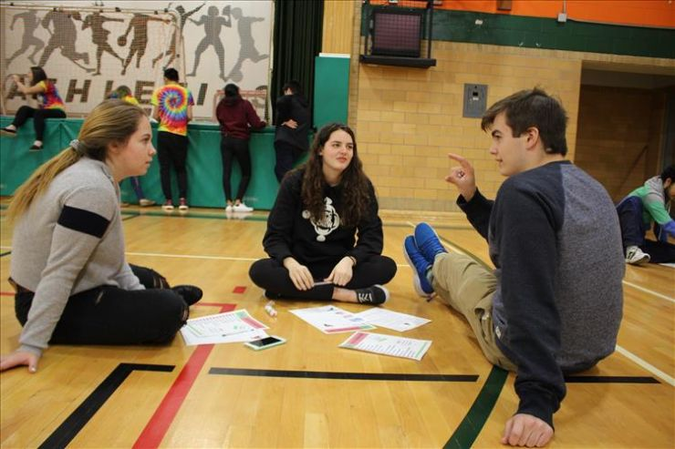 Three students seated in a gym make plans