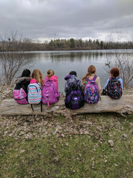 Group of children with backpacks sit on log overlooking lake