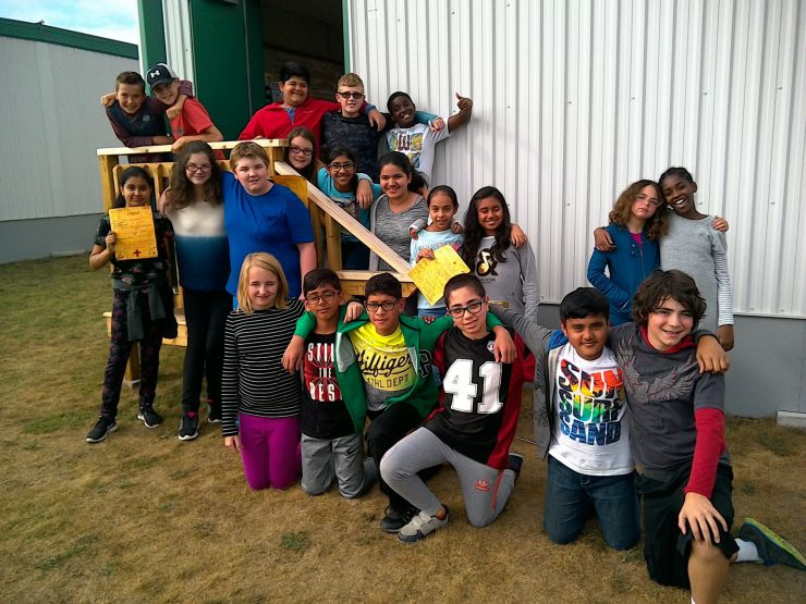 A group of Grade 6 students poses outdoors