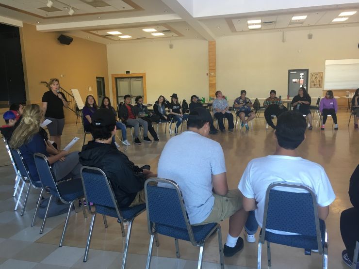 A circle of students listens to a speaker